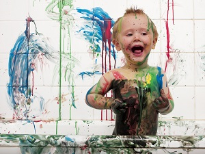 little boy making a mess with paint